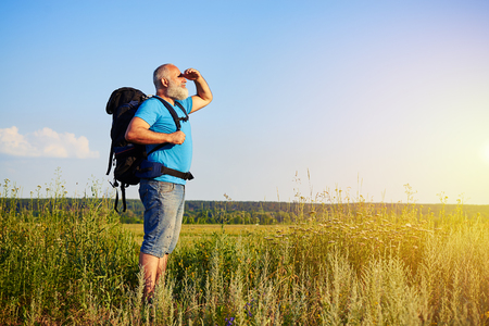 man looking: Physically fit handsome aged man with rucksack is standing in the grass and looking at sunlight