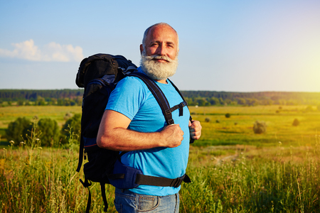 white beard: Active fit aged tourist with white beard is standing with rucksack behind his back against sunlit field background Stock Photo