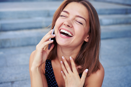 sincerely: Attractive young female is speaking on the phone and laughing sincerely over grey street stairs background