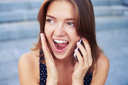 mobile telephone: Young beautiful girl is speaking on the mobile telephone with happy and surprised expression on her face Stock Photo