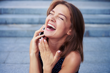 sincerely: Attractive cheerful female is speaking on the phone and laughing sincerely over grey street stairs background Stock Photo