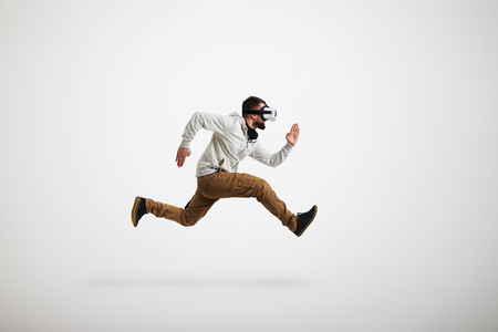 midair: Young bearded man in virtual reality headset is photographed in mid-air jump isolated on white background