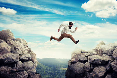 between: Young man in casual clothes and virtual reality headset is jumping between two high rocks on the background of blue sky and green valley
