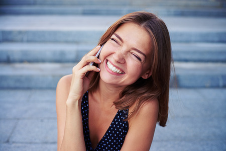 Cheerful young beautiful woman is laughing with eyes closed while talking on the phone on the street