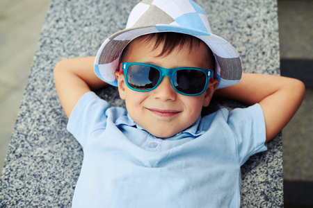 parapet: Close-up of small boy in sunglasses and hat who is lying with hands under his head on street stairs parapet and smiling