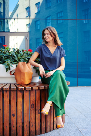 flower pot: Elegantly dressed young beautiful woman is sitting on round bench with flower pot in the middle on mirror glass building background Stock Photo