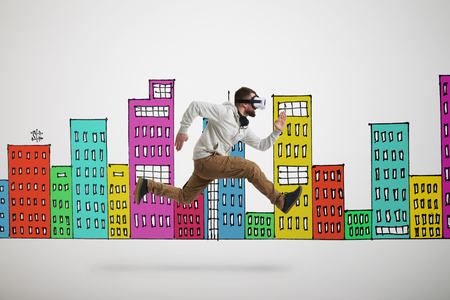 midair: Young bearded man in virtual reality headset is photographed in mid-air jump isolated over white background with colorful buildings drawn on it Stock Photo