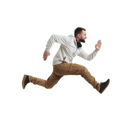 Young bearded man in casual clothes is shot in mid-air jump isolated over white background