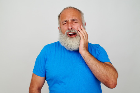 screaming: Bearded male in blue T-shirt is touching his cheek as if suffering from toothache isolated against white background Stock Photo