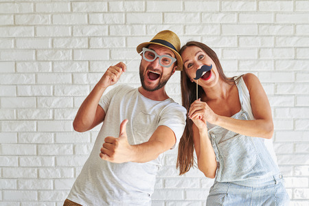 funny glasses: Funny couple holding paper moustache and glasses, they are laughing