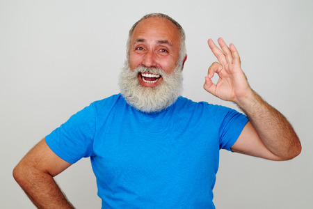 white beard: Aged man with white beard and broad smile is standing against white background and showing OK gesture Stock Photo