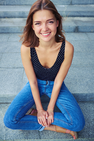 skinny jeans: Cheerful young girl sitting in yoga pose and smiling. She is relaxed and happy she wears denim skinny jeans and a T-shirt Stock Photo