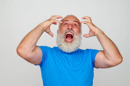 expressive: Stylish aged man with white beard is posing at the camera expressing anger isolated on blank white background