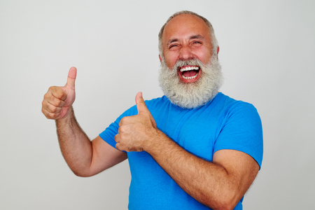sincerely: Joyful aged man is smiling sincerely and giving two thumbs up against white background