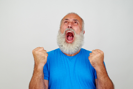 fury: Aged man with white beard is screaming in fury with mouth widely opened and clenched fists isolated against white background