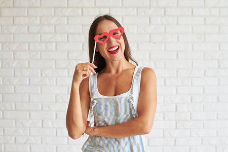 white singlet: Happy smiling woman wear white singlet with overalls and holding red glasses-mask in the shape of heart, white brick wall on background