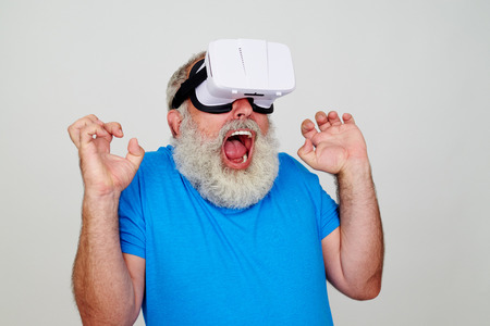 freaked: Aged bearded man in 3D virtual reality glasses is freaked out while testing virtual reality technology isolated against white background