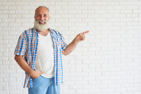 white beard: Smiling stylish senior point his finger to the side, white brick wall in background