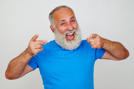 mouth smile: Senior man with white beard in bright blue T-shirt looks delighted against white background Stock Photo