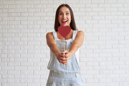 white singlet: Happy beautiful brunette dressed in singlet with overalls and holding red paper heart in front of her, white brick wall on background