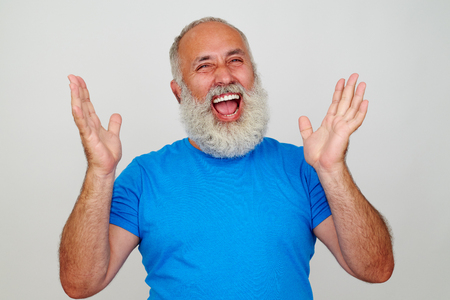 lifted hands: Aged stylish man in blue T-shirt is laughing sincerely with hands lifted isolated on white background