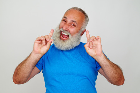 persona mayor: Senior stylish man with white beard is posing at the camera expressing happiness and joy against white background