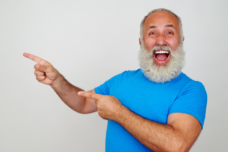right on: Aged bearded male is gesturing happiness and pointing with fingers to his right side on white background