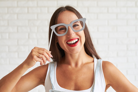 Young smiling woman wear white singlet and holding glasses-mask, white brick wall on background