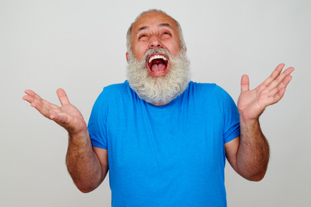 Fit aged bearded man is overwhelmed with positive emotions and looks very happy