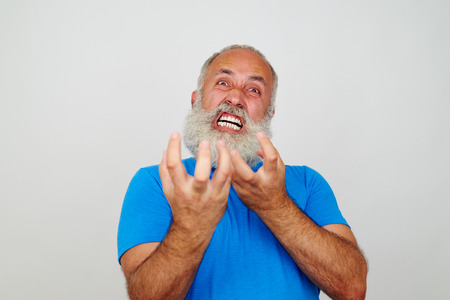 nervousness: Aged bearded man is grimacing at the camera expressing extreme nervousness isolated on white background