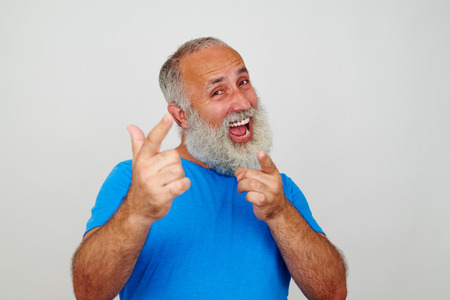 energetically: Good-looking elderly man is energetically pointing at the camera with his fingers on white background
