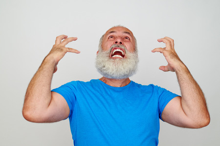 nervousness: Man with white beard is infuriated and nervous isolated against white background Stock Photo