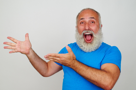 Senior white-bearded man is delighted and pointing with both hands at something on his right side