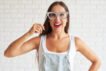 holds: Young smiling woman wear white singlet and holding big glasses-mask, white brick wall on background