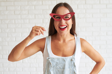 white singlet: Happy smiling woman wear white singlet and holding red glasses-mask, white brick wall on background
