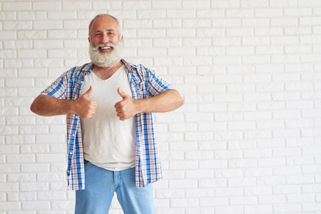 show of hands: Smiling stylish senior dressed in jeans and checkered shirt show thumbs up with both hands, white brick wall in background