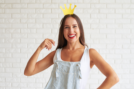 white singlet: Happy smiling woman wear white singlet and holding decorate crown, white brick wall on background