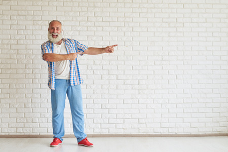 Senior souriant habillé debout à la mode et pointe des deux mains sur le côté, mur de briques blanches en arrière-plan