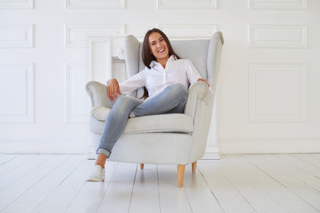 whose: Close-up of Caucasian modern positive woman whose face shows kindness, she crossed one leg while sitting in the armchair