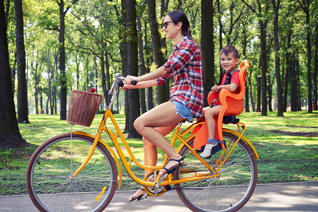 riding: Positive family of mother and her son riding a bike together on a bright sunny day in the park