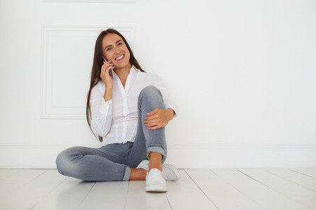 contented: Contented carefree woman talking on smartphone and expressing kindness while sitting on the floor