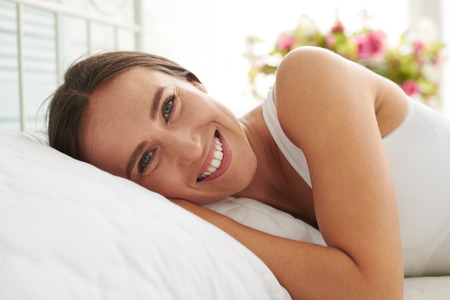sleepwear: Close-up portrait of young Caucasian woman lying on the bed and smiling early in the morning Stock Photo