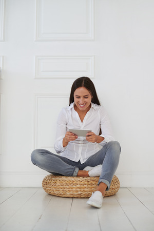 hassock: Young attractive businesswoman sitting with crossed leg and holding tablet on a hassock, she is wearing casual outfit Stock Photo