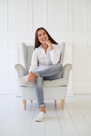 mujer sentada: Primer plano de mujer hermosa feliz sosteniendo su cabeza, cruzó la pierna y relajante mientras está sentado en un sillón cómodo Foto de archivo