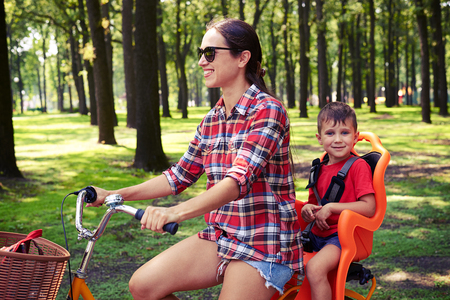 mom son: Mom and her small son prefer a healthy lifestyle. They are eager to start the day with a bicycle ride along the park. They are wearing casual outfits