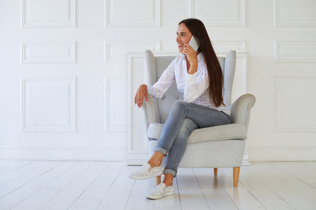 contented: Contented attractive young woman in casual clothes having conversation on the mobile phone while sitting in the armchair