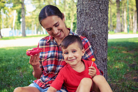 Happy joyful young mom and her son while having good time in the park, they are sitting on the grass and holding sweats on a sunny summer day Stock Photo