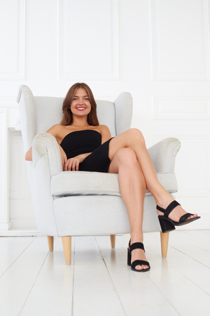 A nice picture of a lovely, beautiful, happy women in a small black dress sitting on a white armchair