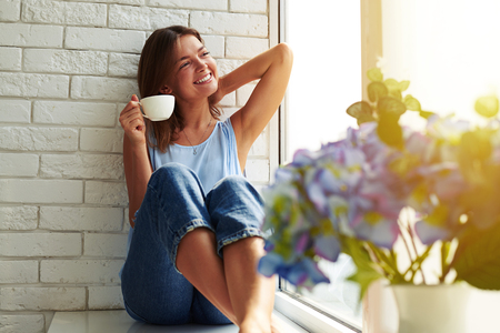 The perfect morning relation with a cup of aroma coffee. Young girl in a casual stylish suit basking in the peaceful atmosphere. She looks calm, happy and relaxed while sitting on the window-sill.