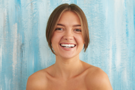 junge nackte mädchen: The sunny engaging smile of young sensual attractive pretty nude girl, posing against a blue background